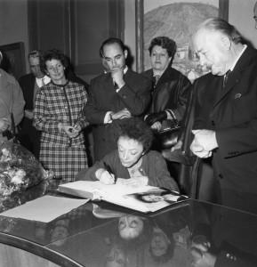 Edith Piaf signe le livre d'or de la ville. Derrière elle, Guy Henras et le maire à droite